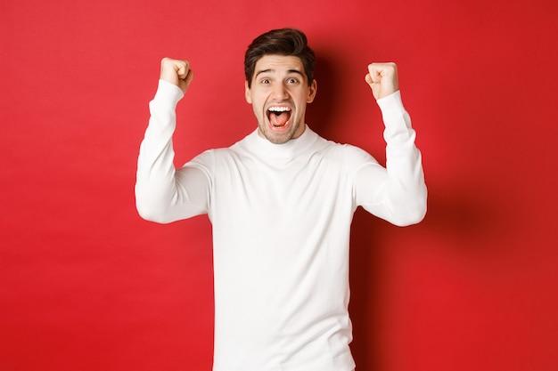 Ritratto di uomo fortunato eccitato in maglione bianco alzando le mani e trionfando festeggiando il nuovo anno ...