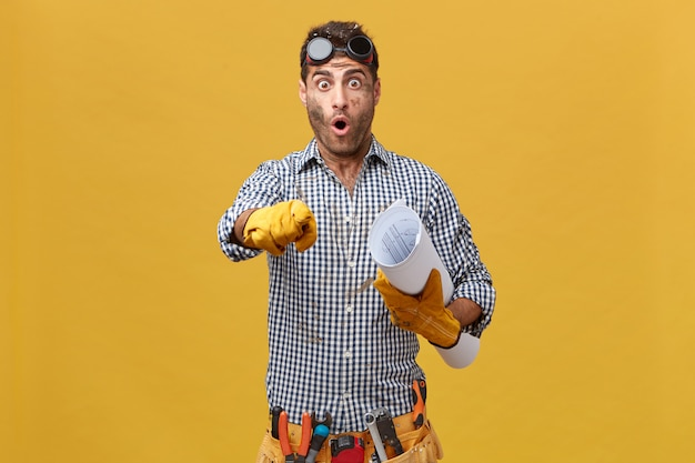 Portrait of excited male plumber wearing protective eyeglasses, checkered shirt, belt with instruments holding paper in hand pointing with forefinger. professional workman looking puzzled