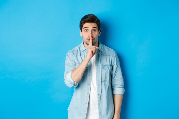 Portrait of excited man asking to keep quiet, showing hush taboo sign and looking nervously at camera, standing against blue background