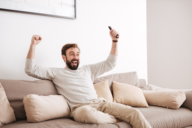 Portrait of an excited man holding remote control
