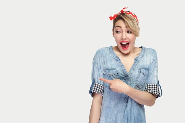 化粧、赤いヘッドバンドが立って背景のコピースペースを指してカジュアルな青いデニムシャツで美しい若い女性の興奮した肖像画。白い背景で隔離の屋内スタジオショット。
