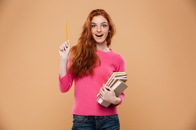 Portrait of an excited pretty redhead girl holding books and having an idea
