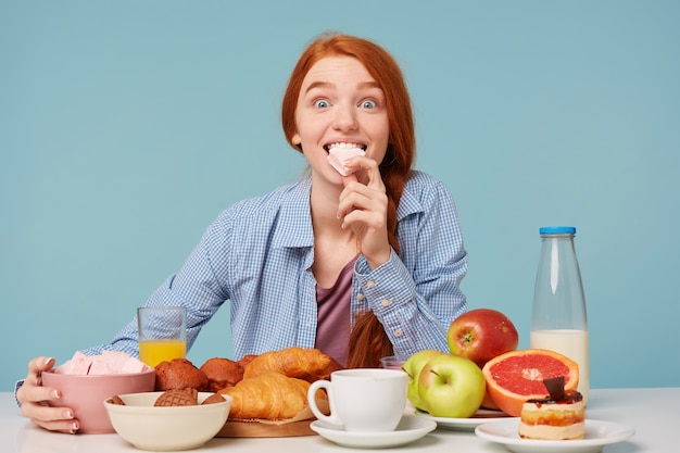 Portrait of an excited red haired woman holding marshmallow and having a variable breakfast
