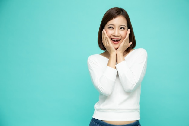 Portrait of excited screaming young asian woman standing isolated
