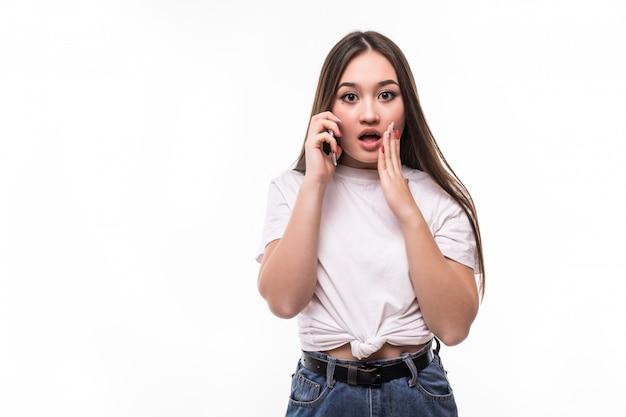 Ritratto di una donna asiatica colpita emozionata che parla sul telefono cellulare e che gesturing sopra la parete bianca