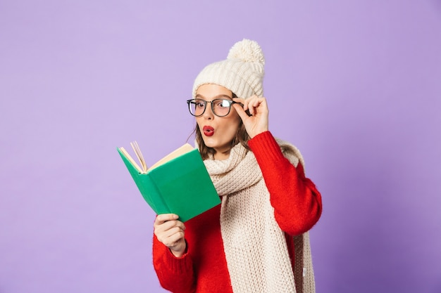 Portrait of an excited shocked young woman wearing winter hat isolated over purple wall reading book.