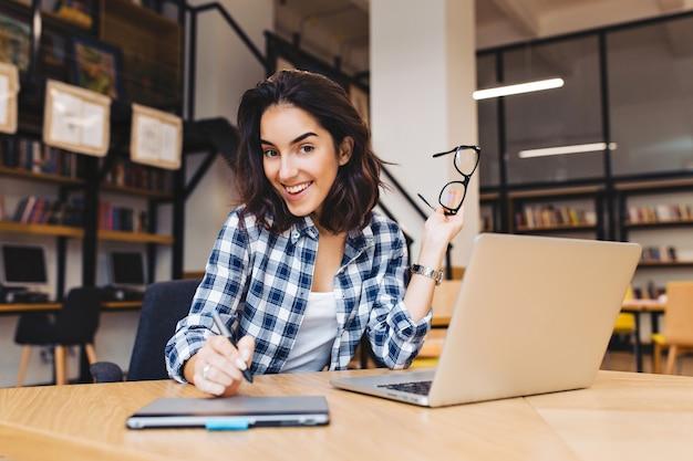 초상화 흥분 미소 갈색 머리 젊은 여자 도서관에서 노트북으로 작업. 영리한 학생, 대학 생활, 인터넷에서 일하고, 웃고, 쾌활한 분위기.