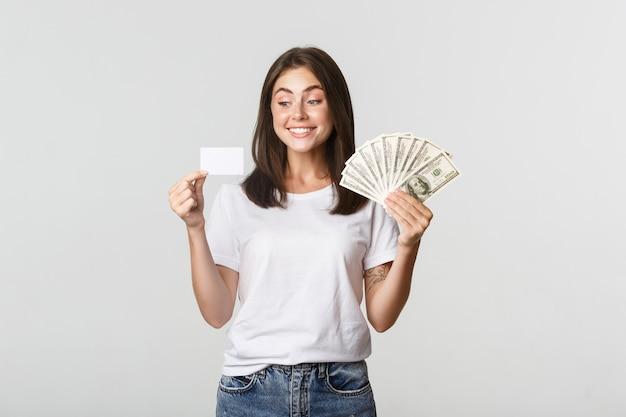 Ritratto della ragazza sorridente eccitata che tiene soldi e carta di credito, bianco.