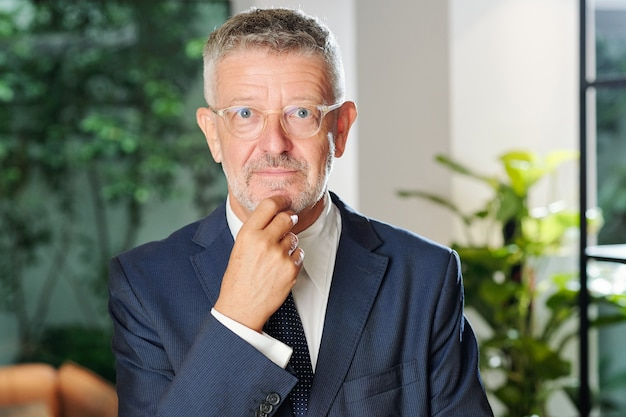 Portrait of excited smiling senior businessman in glasses touching chin