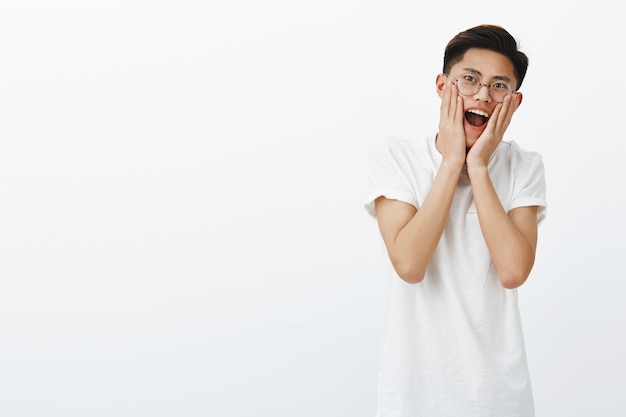 Portrait of excited surprised and charismatic young attractive asian male model with stylish hairstyle in round glasses dropping jaw and screaming from joy pressing palms to cheeks impressed