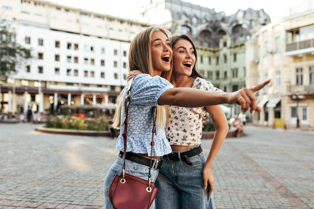 Portrait of excited surprised girlfriends in stylish jeans and floral blouses pose outside