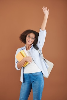 Portrait of excited teenage girl with students book waving with hand