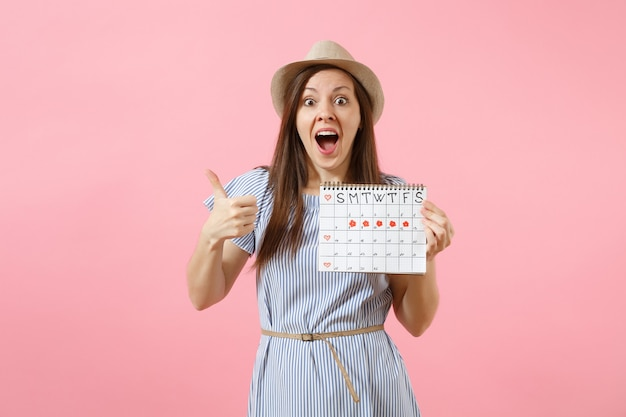 Portrait of excited woman in blue dress, hat holding periods calendar for checking menstruation days isolated on bright trending pink background. medical, healthcare, gynecological concept. copy space