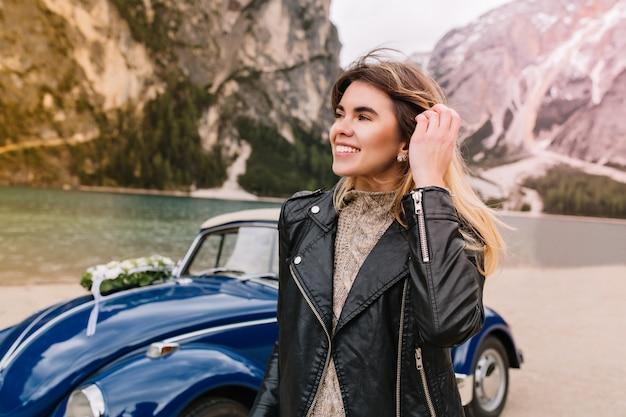 Ritratto di donna eccitata che tocca i suoi capelli e distoglie lo sguardo con il sorriso che cammina vicino al lago