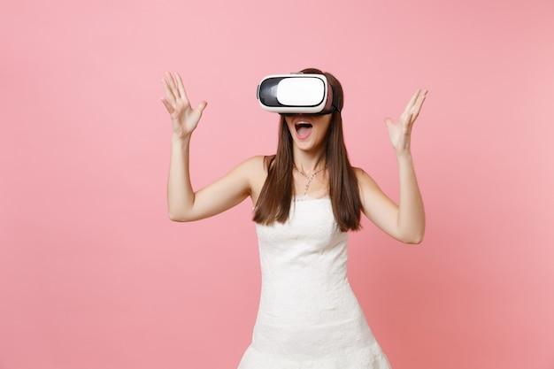 Ritratto di donna eccitata in abito bianco, cuffia di realtà virtuale che allarga le mani