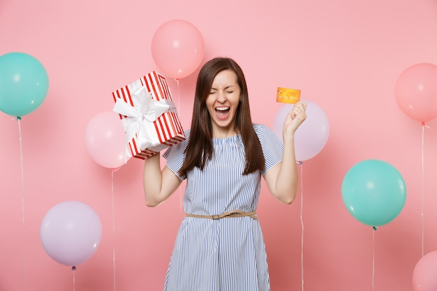Portrait of excited woman with closed eyes in blue dress hold credit card and red box with gift present on pink background with colorful air balloon. birthday holiday party, people sincere emotions.
