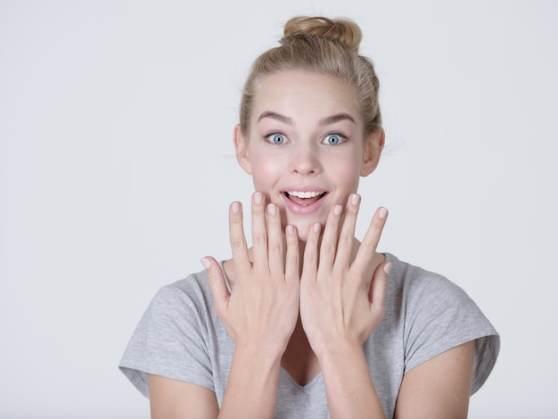 Ritratto di una donna eccitata con emozioni positive, su sfondo bianco