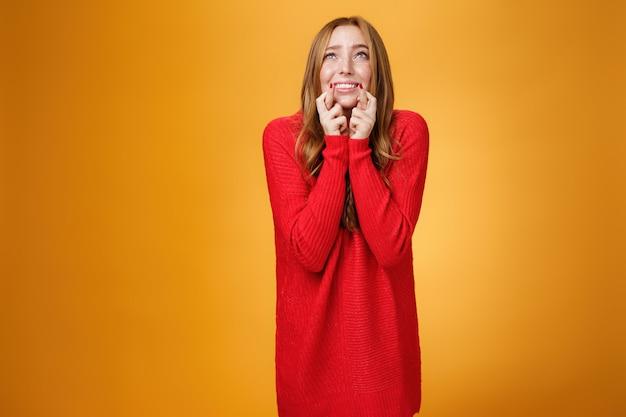 Ritratto di giovane donna rossa eccitata e preoccupata negli anni '20 chinandosi in piedi in posa di accattonaggio incrociando il dito per buona fortuna guardando il cielo come pregando dio e chiedendo aiuto con il desiderio che si avvera