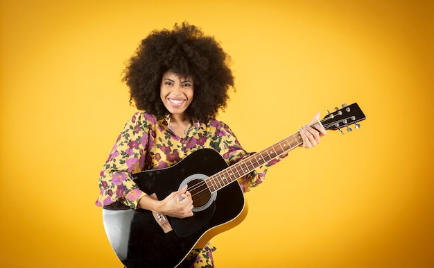 Portrait of excited young african american woman with a bright smile dressed in casual clothing dancing with a guitar over yellow background