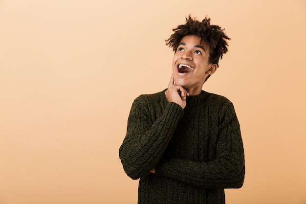Portrait of an excited young african man dressed in sweater isolated over beige wall, looking away at copy space