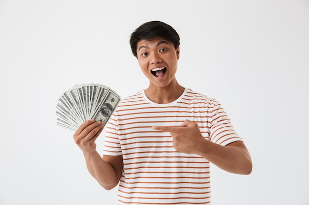 Portrait of an excited young asian man pointing finger