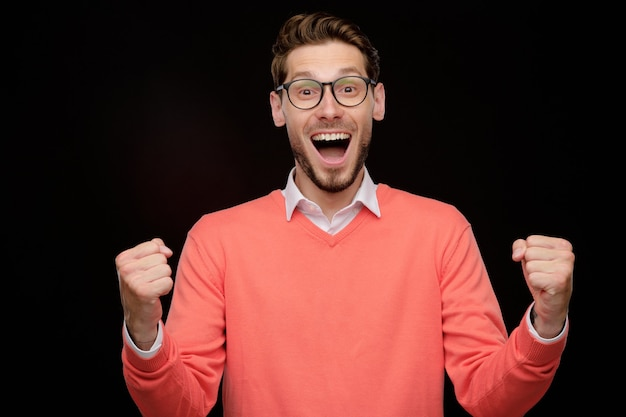 Portrait of excited young bearded man with open mouth making yes gesture while winning prize, black background