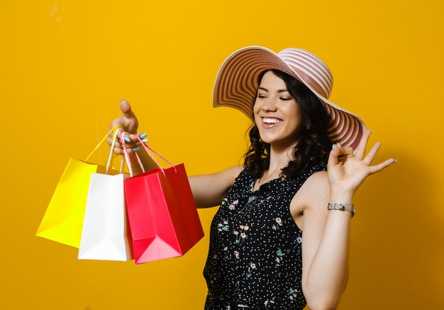 Portrait of a excited young  beautiful asian girl holding a gift and happy over yellow wall