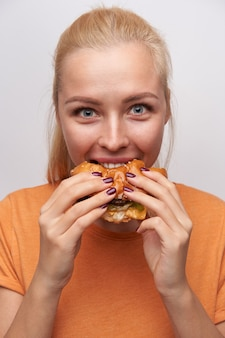Portrait of excited young blue-eyed pretty blonde woman eating eagerly her burger and rounding eyes while looking joyfully at camera, posing over white background in casual clothes