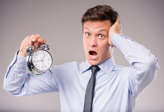 Portrait of excited young businessman holding a clock.