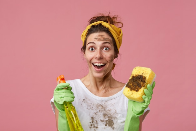 Portrait of excited young female doing housework, cleaning furniture, holding dirty sponge and detergent having surprised look to see so much dust. astonished housewife isolated over pink wall
