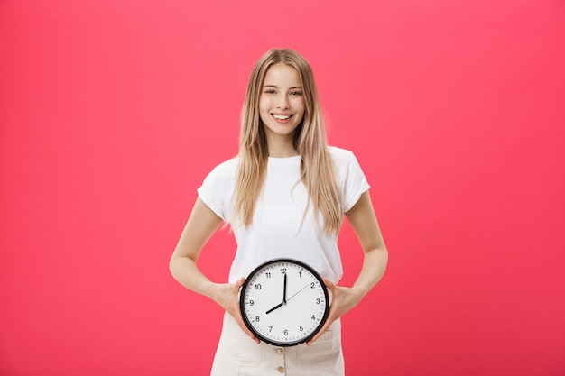 Portrait of an excited young girl dressed in white t-shirt pointing at alarm clock