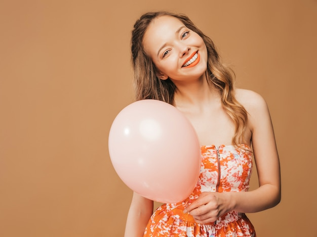 Portrait of excited young girl posing in trendy summer colorful dress. smiling woman with pink balloon posing. model ready for party