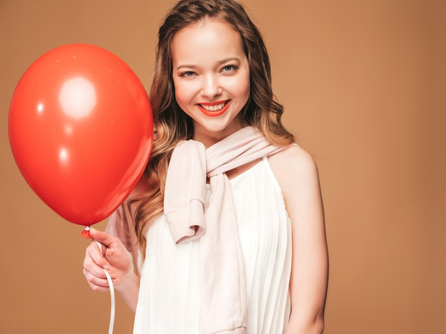 Portrait of excited young girl posing in trendy summer white dress. smiling woman with red balloon posing. model ready for party