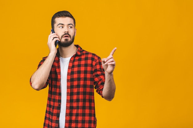 Portrait of an excited young man in casual using mobile phone while pointing finger up isolated over red wall.