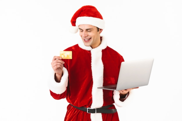 Portrait of an excited young man dressed in santa claus costume standing isolated over white space, holding laptop computer