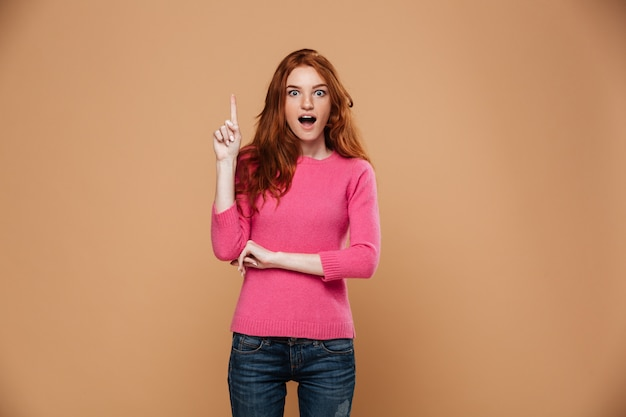 Portrait of an excited young redhead girl pointing up with fingers