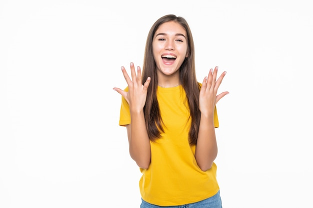 Portrait of a an excited young woman celebrating success over white wall