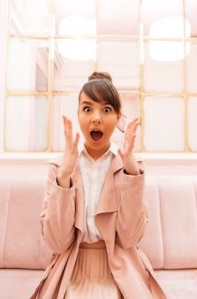Ritratto di una giovane donna emozionante nella seduta del cappotto