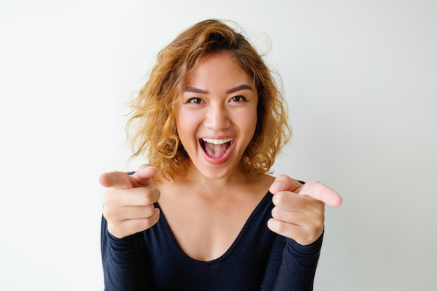 Portrait of excited young woman pointing at camera