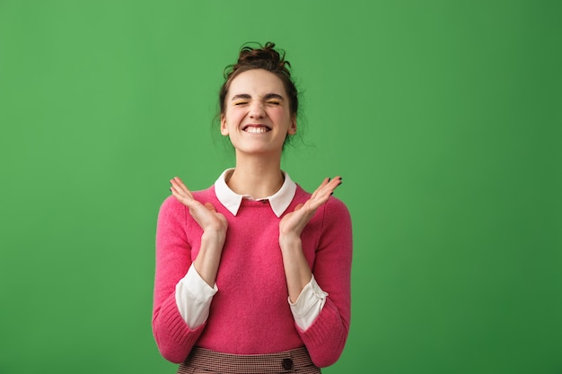 Portrait of an excited young woman screaming isolated over green