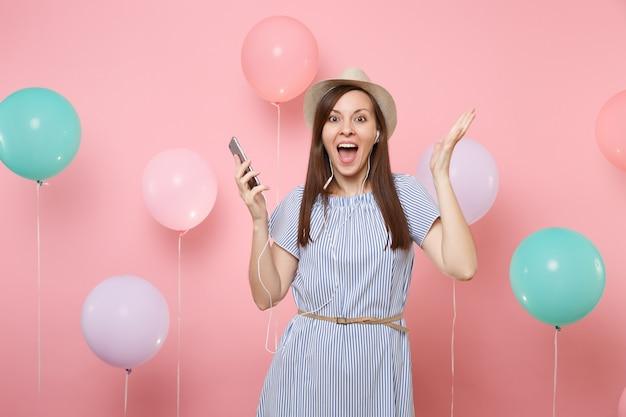 Portrait of excited young woman in straw summer hat and blue dress with mobile phone and earphones listening music spreading hand on pink background with colorful air balloons. birthday holiday party.