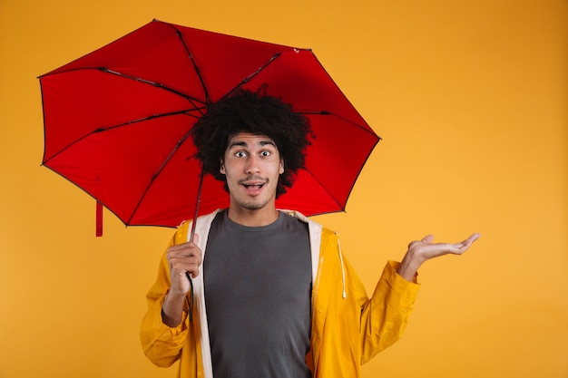Portrait of an exciting afro american man dressed in raincoat