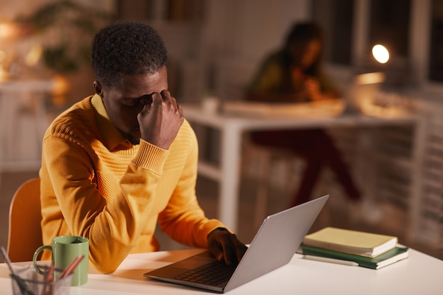 Portrait of exhausted african-american man rubbing eyes while working late at night in dark office, copy space