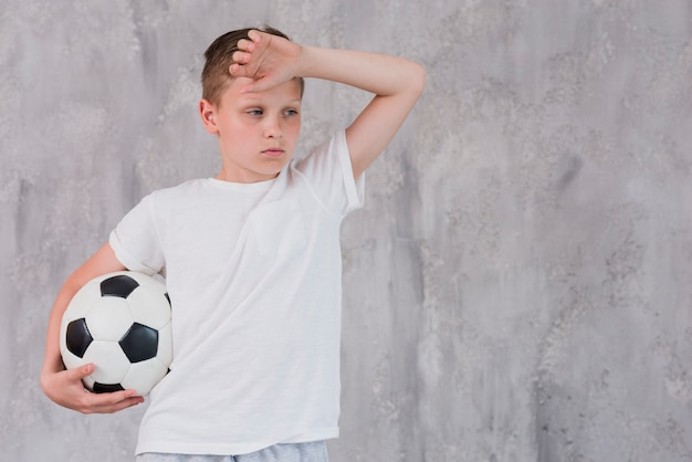 Portrait of a exhausted boy holding soccer ball in hand against concrete wall