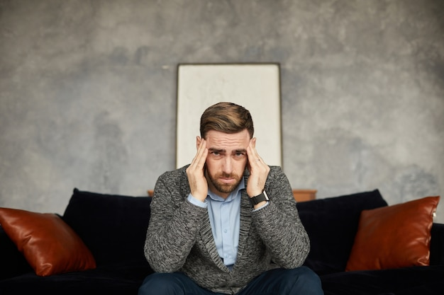 Portrait of exhausted businessman holding his head with his hands and while sitting on sofa