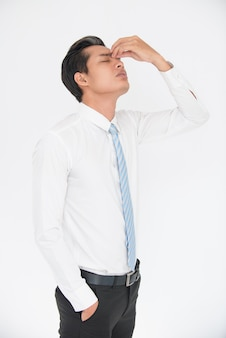 Portrait of exhausted businessman rubbing nose