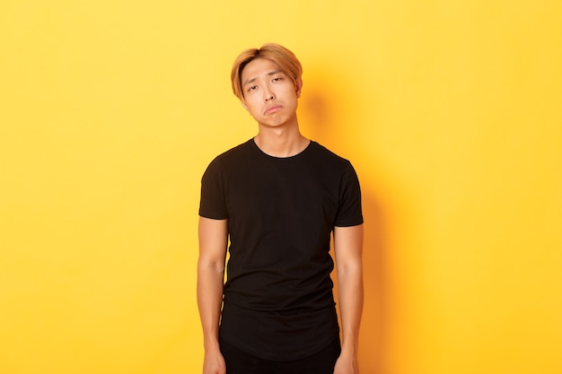 Portrait of exhausted and sad asian guy looking sad, standing drained over yellow wall
