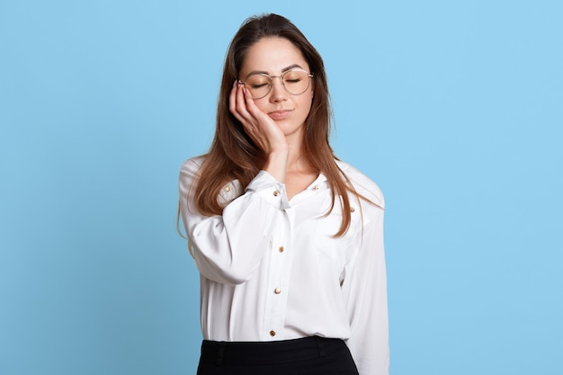 Portrait of exhausted sleeping businesswoman holding her head with closed eyes on right hand.