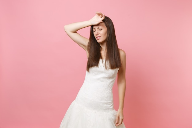 Portrait of exhausted woman in white dress keeping hand on forehead tired