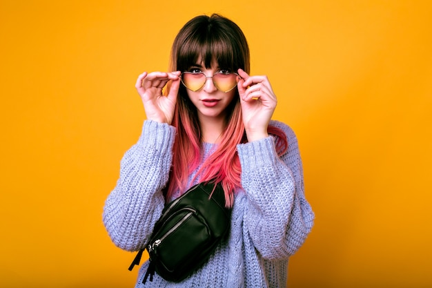 Portrait of exited happy woman with unusual trendy ombre pink hairs posing at yellow wall, surprised emotions, cozy sweater and vintage sunglasses.